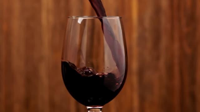 rosenwein aus der flasche gießen. sommelier gießt einen ausgezeichneten rotwein in glas - weinglas stock-videos und b-roll-filmmaterial