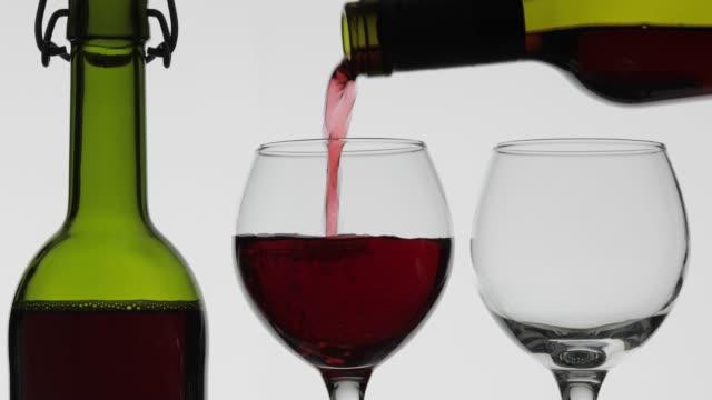ローズワイン赤ワインは白い背景の上に2つのワイングラスに注ぐ - 赤ワイン点の映像素材/bロール