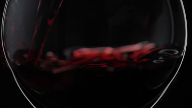 Rose wine. Red wine pour in wine glass over black background. Slow motion Wine. Red wine pouring in wine glass over black background. Rose wine pour into a drinking glass. Silhouette. Close up shot. Slow motion red wine stock videos & royalty-free footage