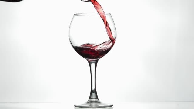 rosenwein. rotwein in weinglas über weißem hintergrund gießen. zeitlupe - weinglas stock-videos und b-roll-filmmaterial