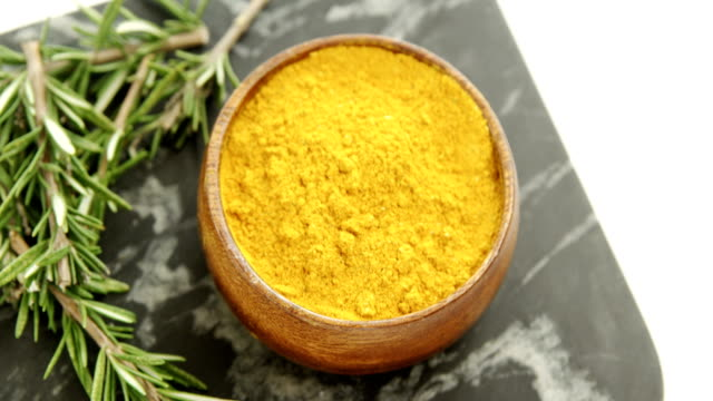 Rosemary with turmeric powder in bowl 4k video