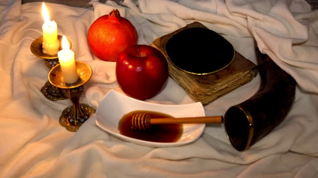 rosh hashanah jewesh holiday concept shofar, torah book, honey, apple and pomegranate. traditional holiday symbols.fullhd video - rosh hashanah filmów i materiałów b-roll