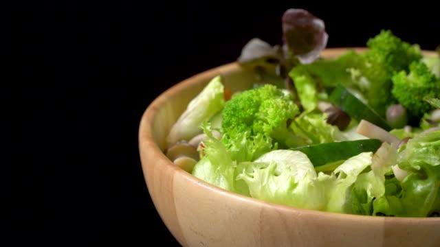vídeos de stock e filmes b-roll de rotate of green salad bowl on black background - saladeira