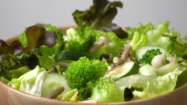 vídeos de stock e filmes b-roll de rotate of green salad bowl on white background - saladeira