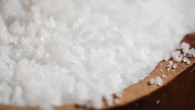 Rotate sea salt flakes on wooden bowl
