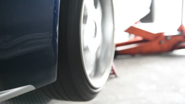 Rotating a car wheels for checking car suspension video