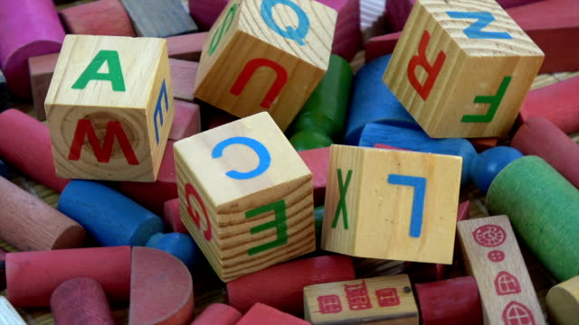 vídeos de stock e filmes b-roll de rotating alphabetical and other toy wooden cubes - bloco