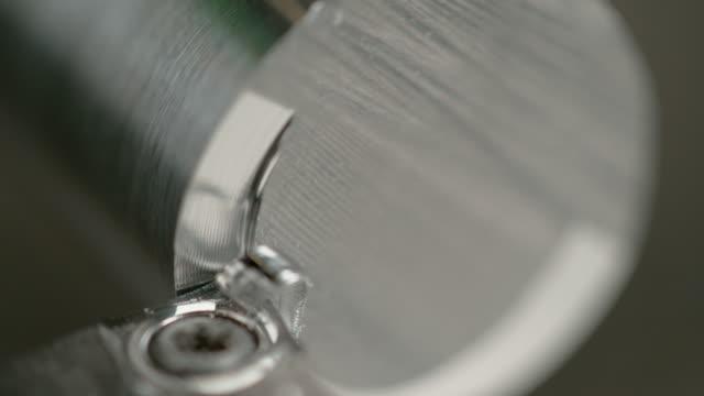 slow motion: rotating aluminium cylinder gets half of its sharp edge shaven off. - spranga video stock e b–roll
