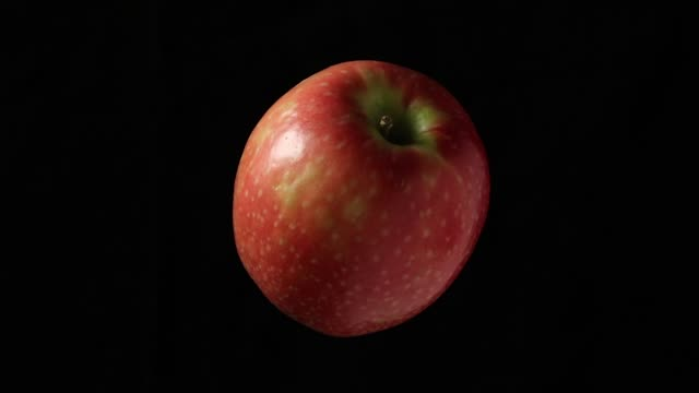 rotating apple on a black background - video