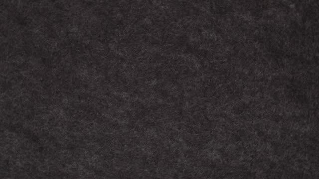 rotating background of black felt - feltro video stock e b–roll