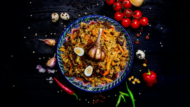 Rotating beautiful dish with pilaf and oriental ornament. Top view video