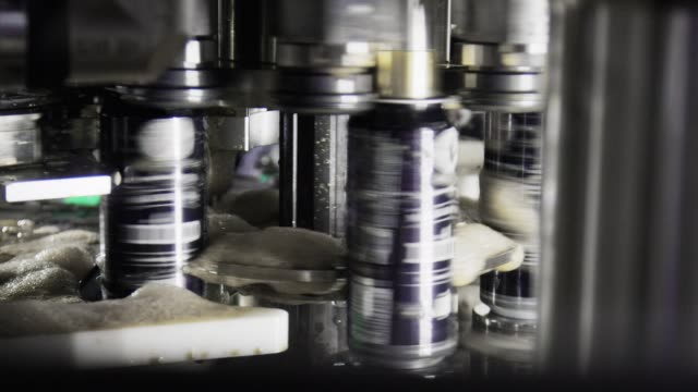 A Rotating Canning Machine Seals Aluminum Cans by Spinning Them in an Indoor Manufacturing Facility