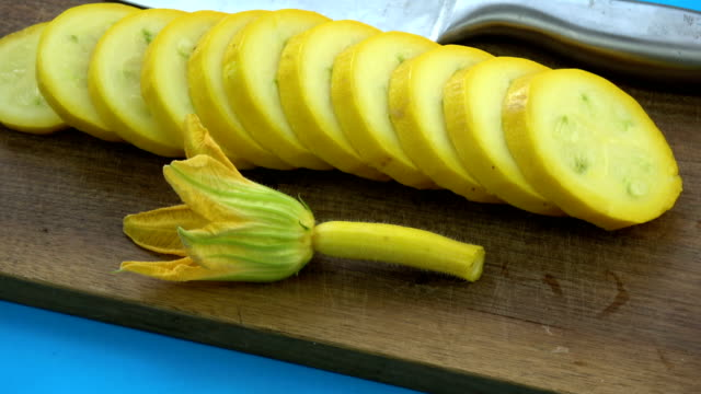 Rotating food background. Courgette slice and kitchen knife video