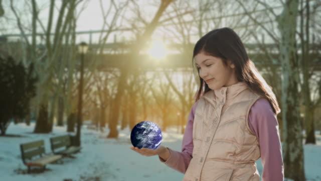 Rotating globe earth girl child holding Human hand Sunlight