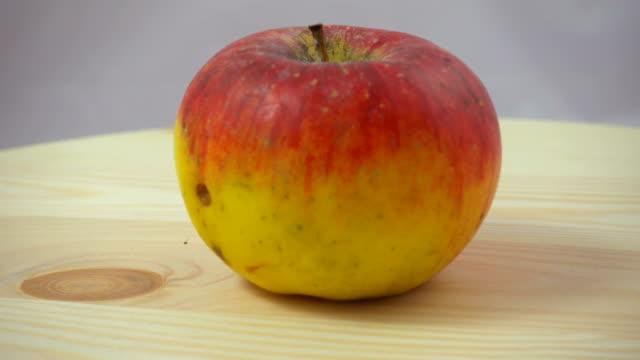 vídeos y material grabado en eventos de stock de rotación imperfecta manzana roja sobre una superficie de woody - imperfección