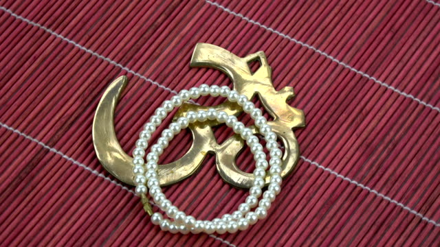 Rotating indian pearls necklace and OM sign on red bamboo mat video
