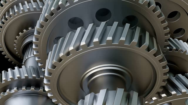 Rotating metal gears, shafts and bearings on black background