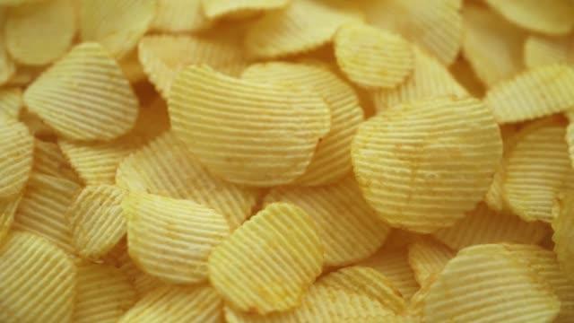 rotating movin texture of corrugated potato crisps with salt close-up - group of people filmów i materiałów b-roll