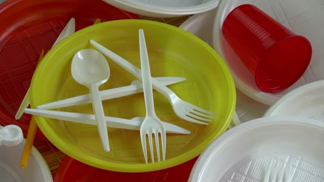 vídeos de stock e filmes b-roll de rotating new colorful plastic disposable tableware - utensílio