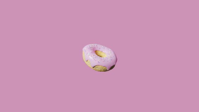 vídeos de stock, filmes e b-roll de donut rosa rotativo - padrão repetido