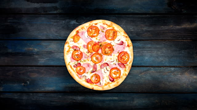 Rotating pizza with ham, mushrooms and tomatoes on a dark wooden background. Top view center orientation video