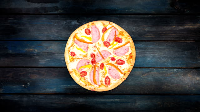 Rotating pizza with ham sweet peppers and tomatoes on a dark wooden background. Top view center orientation video