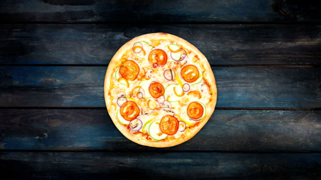 Rotating pizza with slices of tomatoes squash onion and sweet pepper on a dark background. Top view center orientation video