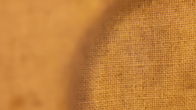 Rotating the burlap texture through a magnifying glass Rotating the burlap texture through a magnifying glass. View from above canvas fabric stock videos & royalty-free footage