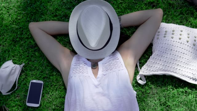 Rotating top view of a Caucasian woman lying on a green field of the park with the face covered by her white hat her white Panama hat and COVID protection mask next to it - City vacation for safety