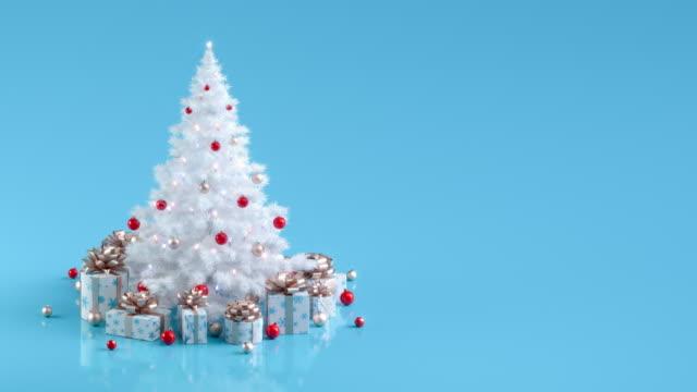 obracająca się biała choinka ze światłami i pudełkami na prezenty - jodła filmów i materiałów b-roll
