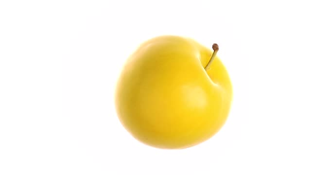 rotating yellow plum on white background - video