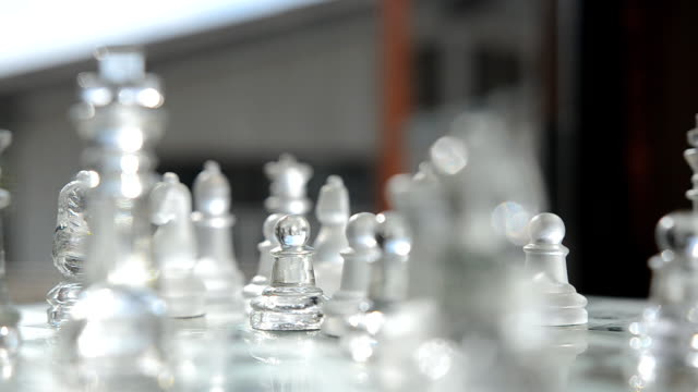 rotation: a pawn among glass chess is behind on window - glass world video stock e b–roll
