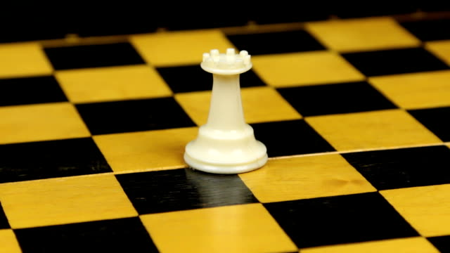 Rotation. Chess figure white rook on chess board.