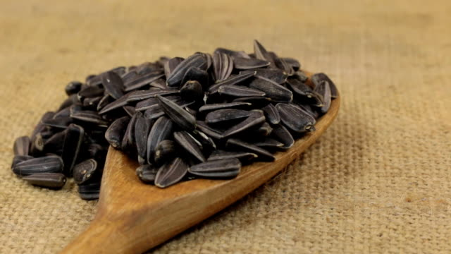 Rotation, heaps of sunflower seeds, falling from a wooden spoon on burlap video