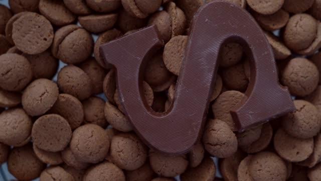stockvideo's en b-roll-footage met rotatie kruidnoten, traditionele sinterklaas snoepjes. nederlandse vakantie sinterklaas achtergrond. pepernoten op het plunderen voor snoep en geschenkdozen.  concept voor sinterklaasdag vijf december. 4k-video - pepernoten