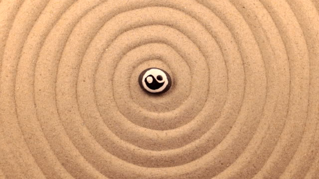 Rotation of a black stone with a yin-yang sign, lying in the center of a spiral made of sand.