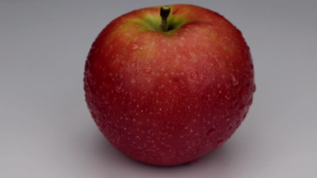 Rotation of a red apple in drops of dew on a white background video