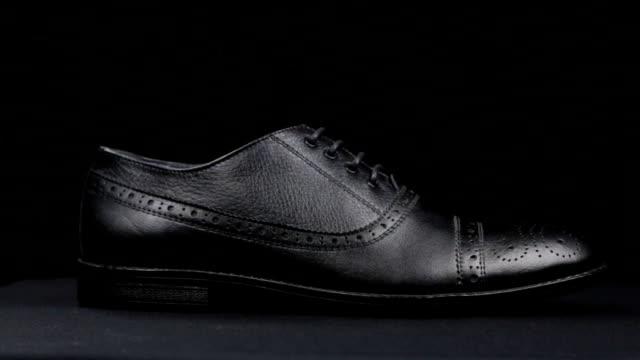Rotation d'une chaussure noire classique élégante avec des lacets sur un fond noir. - Vidéo
