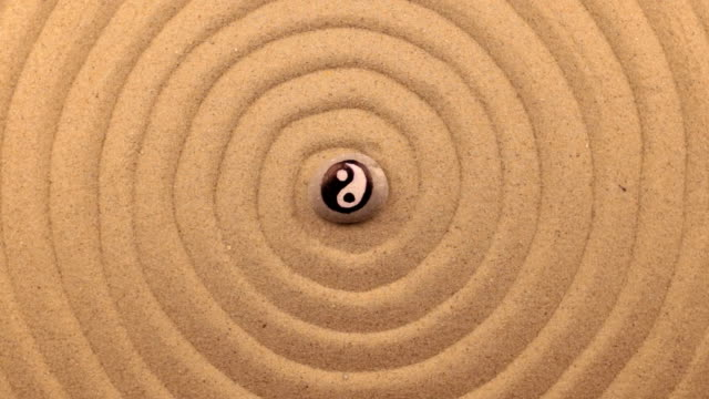 Rotation of a white stone with a yin-yang sign, lying in the center of a spiral made of sand. video