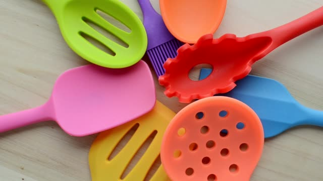 rotation of bright multi colored kitchen utensils on wooden background