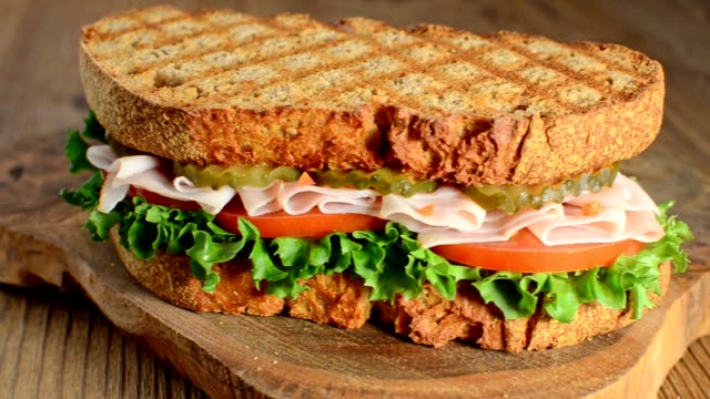 rotation of tasty turkey sandwich with tomato, salad and cucumber, on wooden background rotation of turkey sandwich with tomato, salad and cucumber, on wooden background, selective focus bun bread stock videos & royalty-free footage