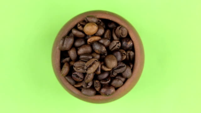 Rotation of the bean of coffee in a pot isolated on green screen. video