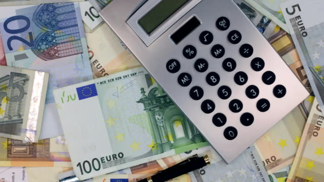 Rotation of the calculator and pen lying on the euros