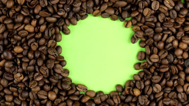Rotation of the coffee beans lying on a green screen, chroma key. video