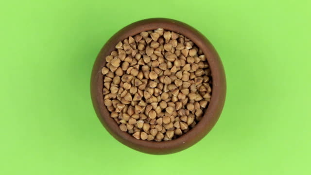 Rotation of the grain of buckwheat in a pot isolated on green screen. video