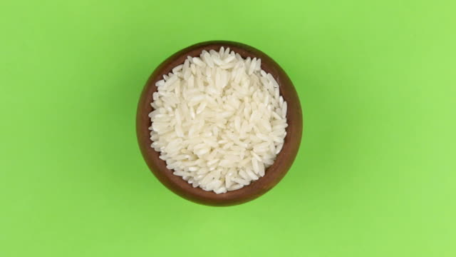 Rotation of the grain of rice in a pot isolated on green screen. video