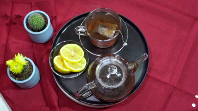 Rotation the black plate with cups of hot tea and lemon .