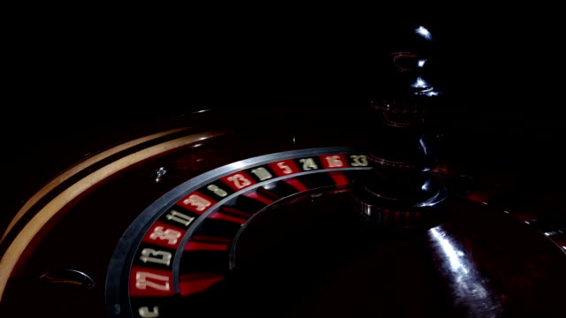 Roulette wheel fast running with white ball, cam moves to the right, on black video