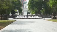istock Round Fountain in the Middle of a Park with People Walking by 1286396668