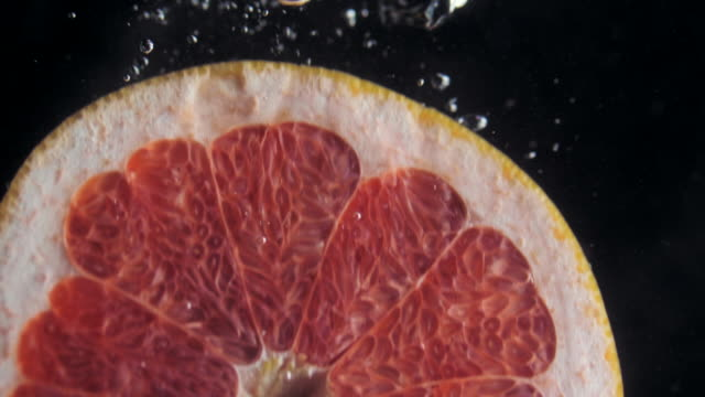 Round fresh juicy grapefruit slice plunging into transparent water with explosive stunning splash. Underwater high-speed slow motion shot on black background. Pomelo isolated video
